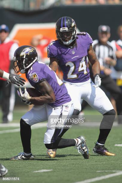 Lardarius Webb of the Baltimore Ravens makes the interception in front of teammate Brandon Carr during their game against the Cincinnati Bengals at...