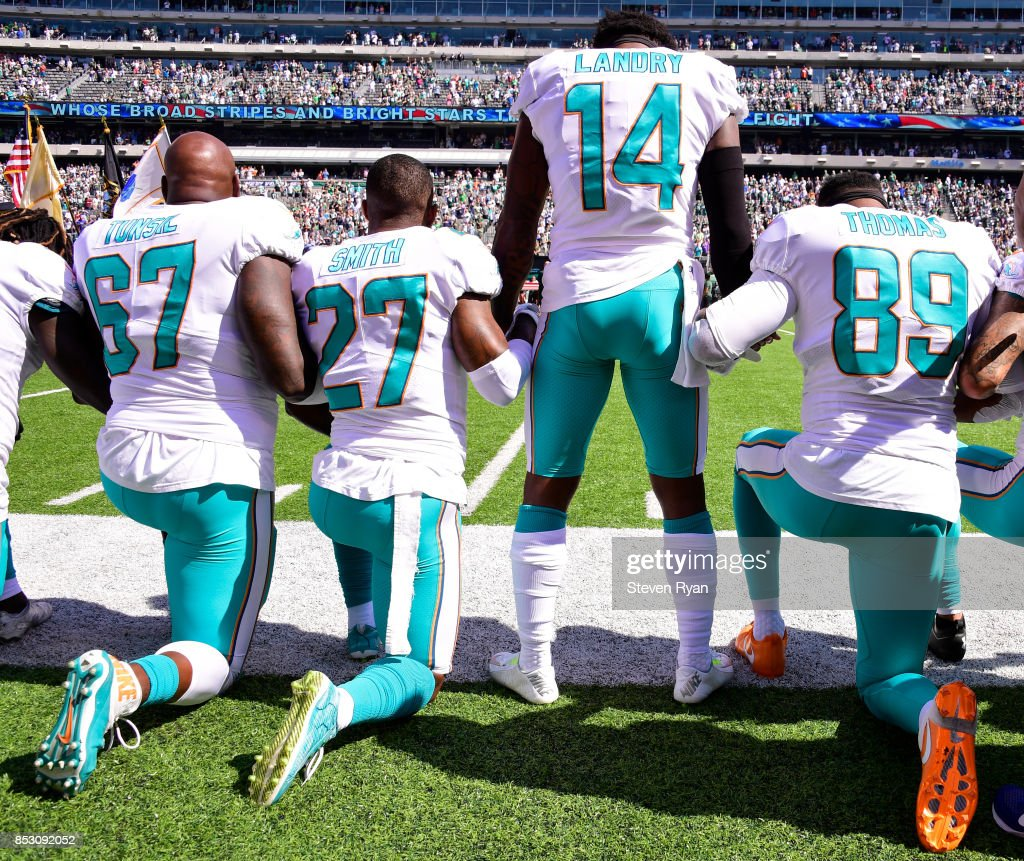 Laremy Tunsil #67, Maurice Smith #27 and Julius Thomas #89 kneel with Jarvis Landry #14 of the Miami Dolphins during the National Anthem prior to an NFL game against the New York Jets at MetLife Stadium on September 24, 2017 in East Rutherford, New Jersey.