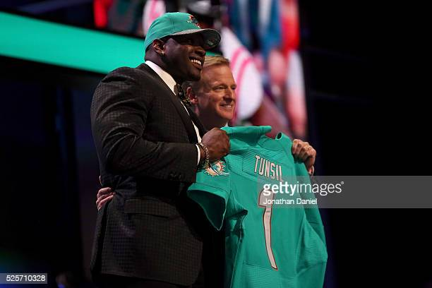 Laremy Tunsil of Ole Miss holds up a jersey with NFL Commissioner Roger Goodell after being picked overall by the Miami Dolphins during the first...