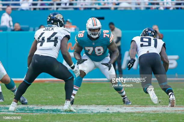 Laremy Tunsil of the Miami Dolphins defends against Myles Jack and Yannick Ngakoue of the Jacksonville Jaguars during an NFL game on December 23 2018...