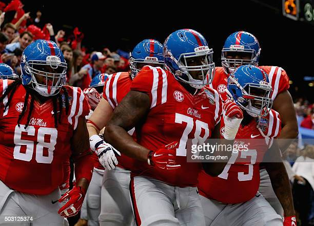Laremy Tunsil of the Mississippi Rebels celebrate his touchdown with teammates during the second quarter against the Oklahoma State Cowboys in the...