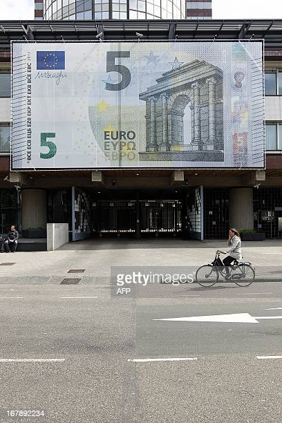 A large 5 eurobanknote hangs on the facade of the Nederlandsche Bank in Amsterdam on May 2 2013 The first series of the lowest value euro banknote...