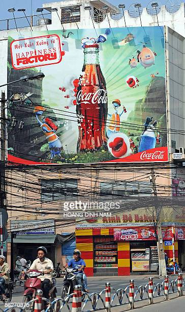 A large advertising billboard for CocaCola looms over a street in downtown Ho Chi Minh city on April 21 2009 Twothirds of Vietnam's population is...