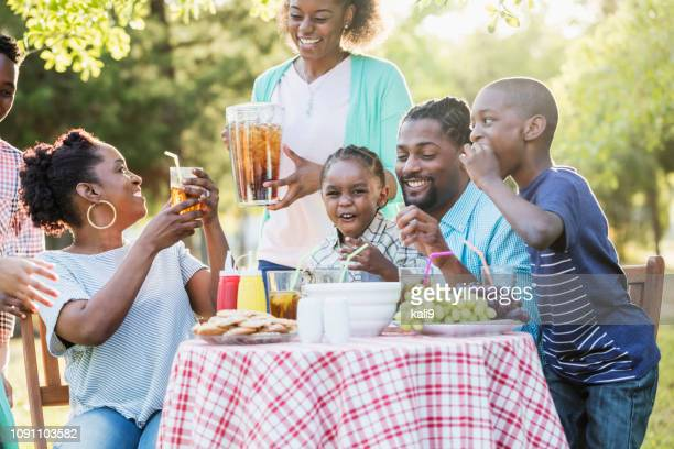 large african-american family having backyard cookout - family reunion stock pictures, royalty-free photos & images