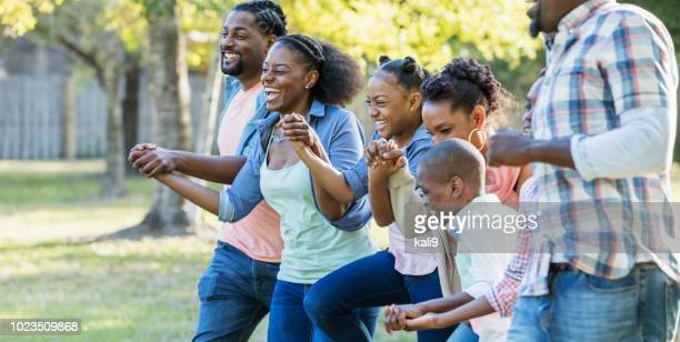 large african-american family running together at park - large family stock pictures, royalty-free photos & images