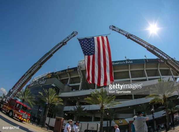 A large American Flag hangs from the ladders of two Jacksonville Fire and Rescue Department Engines during the game between the Tennessee Titans and...