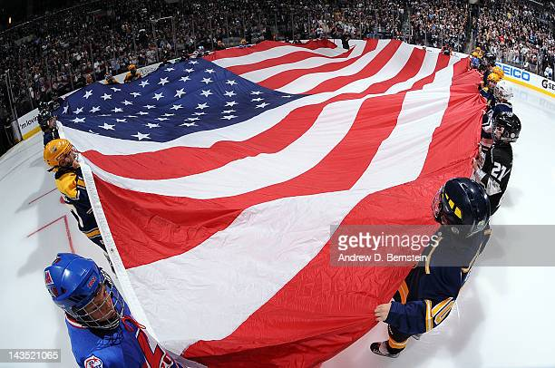A large American flag is held on the ice prior to the game between the Los Angeles Kings and the Vancouver Canucks in Game Four of the Western...