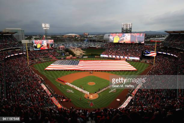 A large American flag is unfurled during introductions of the Los Angeles Angels of Anaheim and the Cleveland Indians prior to the Los Angeles Angels...