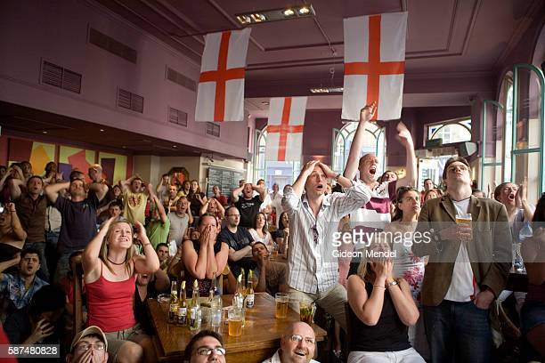 A large and mixed group of England football fans at a central London pub visibly express their anxiety and dissapointment as their team narrowly...