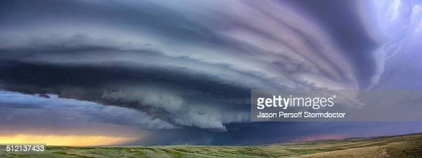 Large arcus cloud sweeps around the updraft of anticyclonic supercell with sunset colors projected on the cloud, Deer Trail, Colorado, USA