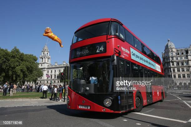 A large balloon depicting London Mayor Sadiq Khan in a yellow bikini floats over an iconic London red bus as demonstrators gather in Westminster in...