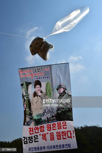 A large balloon is strung with a banner printed with a picture of North Korean leader Kim JongUn as South Korean activists launch large balloons...