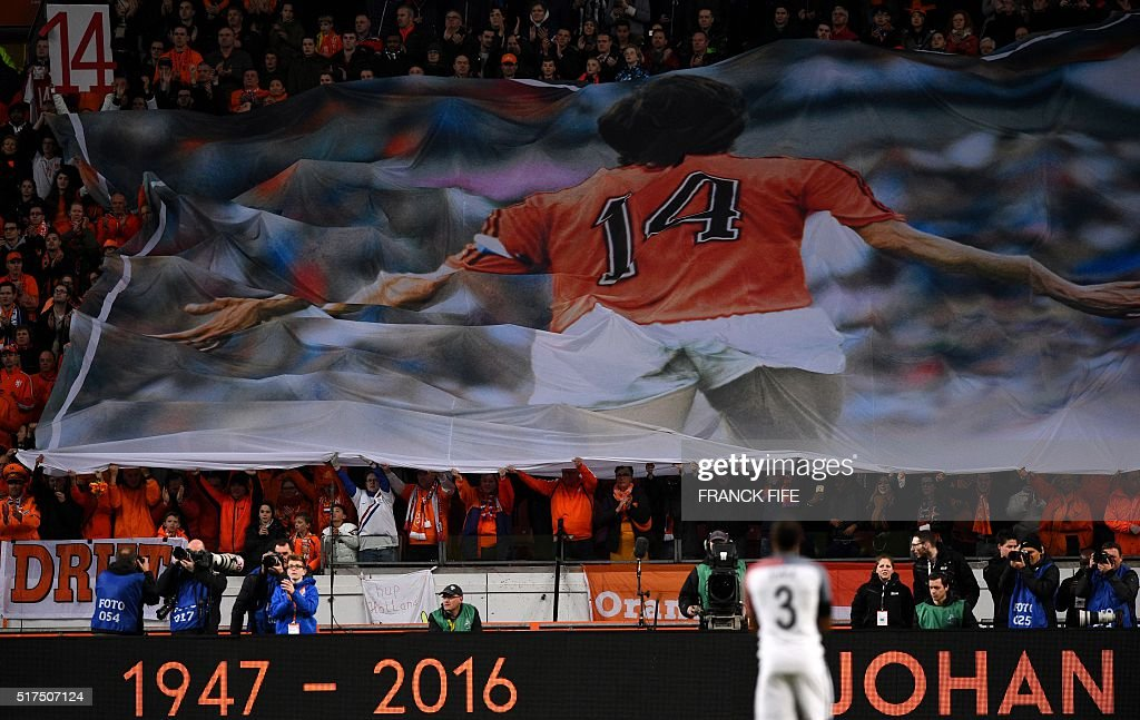 A large banner is displayed during a standing ovation in honour of late Dutch football legend Johann Cruyff during a pause in the 14th minute of the friendly football match between the Netherlands and France at the Amsterdam ArenA, on March 25, 2016, in Amsterdam. Cruyff, who passed away on March 24, 2016 at the age of 68 after a battle with cancer, wore the number 14 on his Ajax and Dutch national shirt during his glittering playing career.