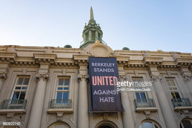 A large banner reading Berkeley Stands United Against Hate hands on the Maudelle Shirek Building at Martin Luther King Jr Civic Center Park in...