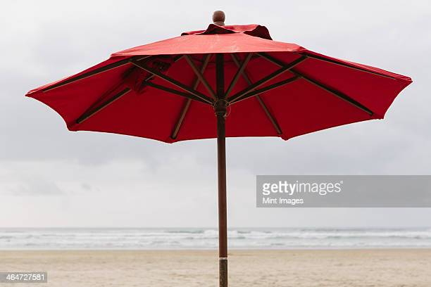 a large beach umbrella on the beach at manzanita, on the pacific ocean in oregon. - manzanita stock pictures, royalty-free photos & images