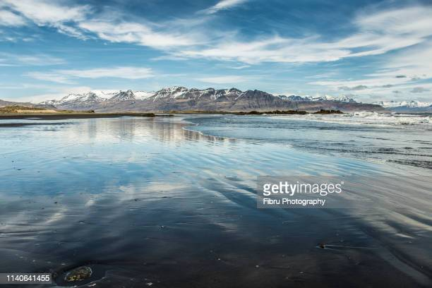 a large beach with blue sky refection and mountains in the background - austurland stock-fotos und bilder