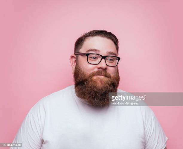 large bearded man on pink background - chubby men stock photos and pictures