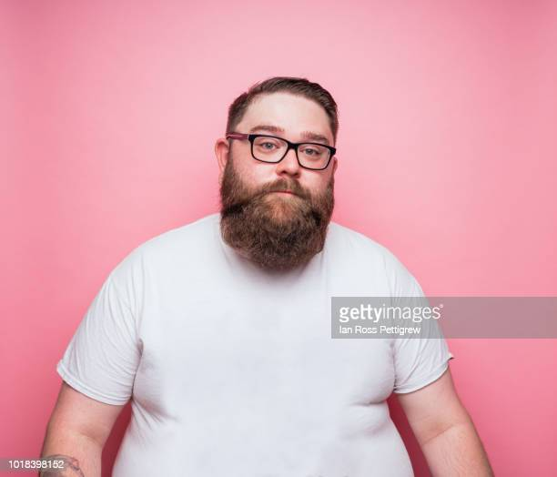 large bearded man on pink background - white t shirt stock pictures, royalty-free photos & images