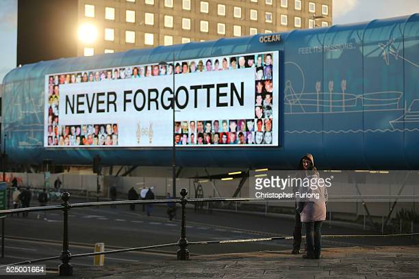 A large bill board displays the words Never Forgotten as people gather outside Liverpool's Saint George's Hall as they attend a vigil for the 96...
