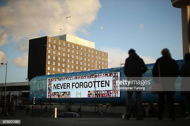 A large bill board displays the words 'Never Forgotten' as thousands of people gather outside Liverpool's Saint George's Hall as they attend a vigil...