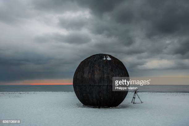 a large black wooden sphere lies on a snow covered shoreline with storm clouds and photographer's tripod - installation art stock pictures, royalty-free photos & images