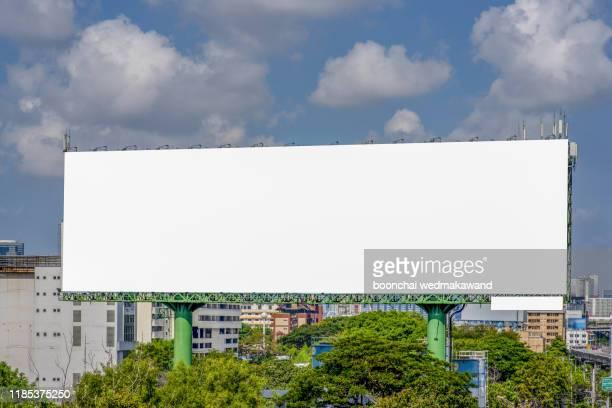 large blank billboard on road with city view background - spruchband stock-fotos und bilder