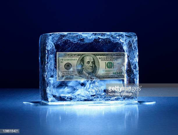 Large block of ice with one hundred dollar bill frozen inside