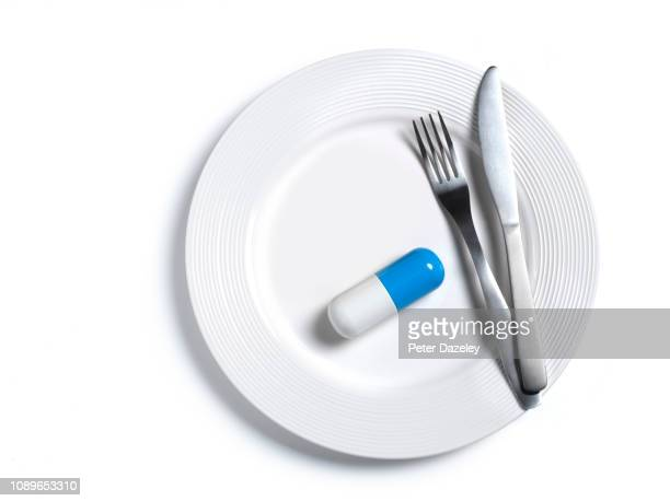 large blue and white pill on plate - capsule stock pictures, royalty-free photos & images