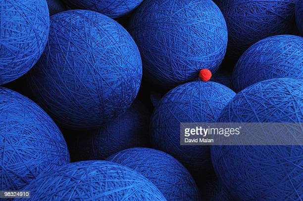 large blue woolen balls with one small red one.