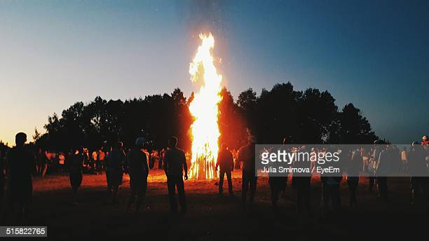 large bonfire surrounded by people - bonfire stock photos and pictures