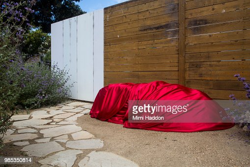 Large Boulder in Front Yard Wrapped in Red Silk Fabric