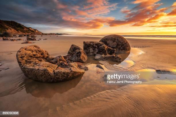 Large boulders at Moeraki Boulders beach during scenic sunrise