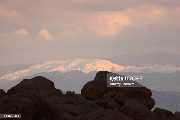 large boulders silhouetted against snowy mountains in late afternoon light near joshua tree national park - timothy hearsum stockfoto's en -beelden