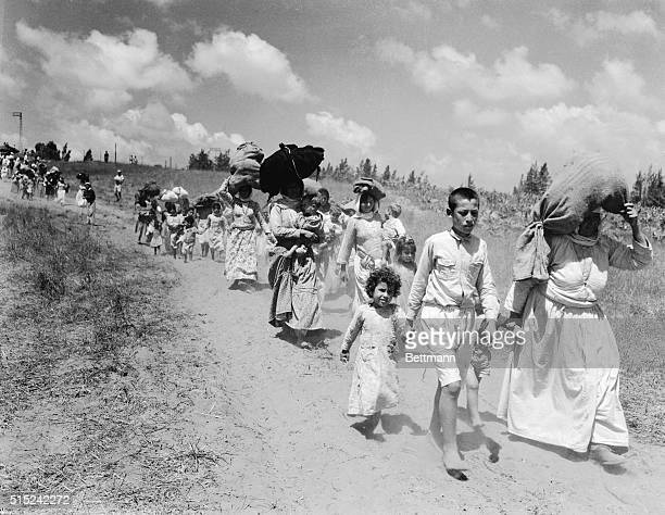 Large bundles of personal possessions are carried on the head of Arab women and children begin a three mile hike through no man's land to the Arab...