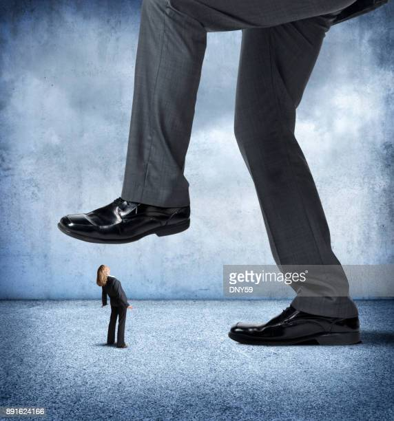 large businessman about to step on small businesswoman - prejudice stock photos and pictures