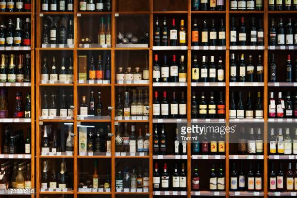 large cabinet with many bottles of wine at supermarket - wine stock pictures, royalty-free photos & images