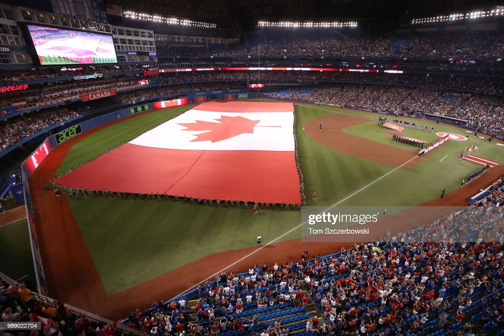 A large Canadian flag is held by members of the military during the singing of the Canadian anthem on Canada Day before the start of the Toronto Blue Jays MLB game against the Detroit Tigers at Rogers Centre on July 1, 2018 in Toronto, Canada.