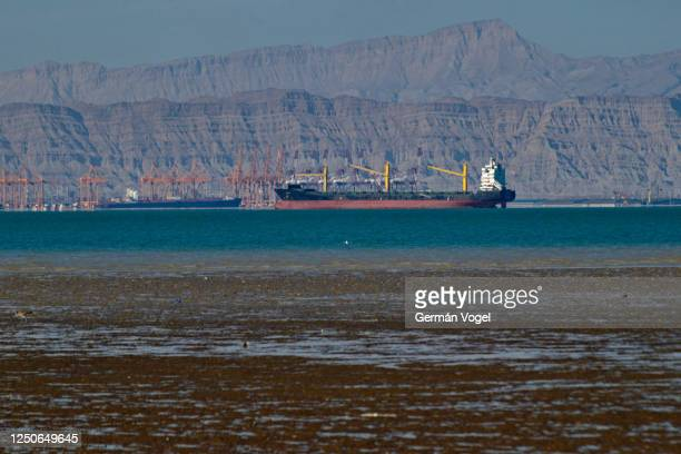 large cargo ship at shahid rajai port from dargahan in low tide from qeshm island, persian gulf, iran - iran stock pictures, royalty-free photos & images