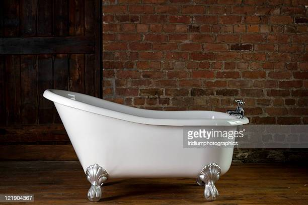 A large claw foot bathtub on a wooden floor