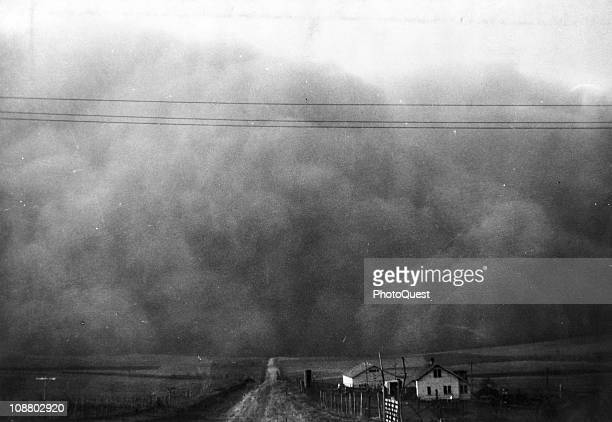 A large cloud of dust is visible on the horizon past some midwestern farmhouses during a dust storm 1935