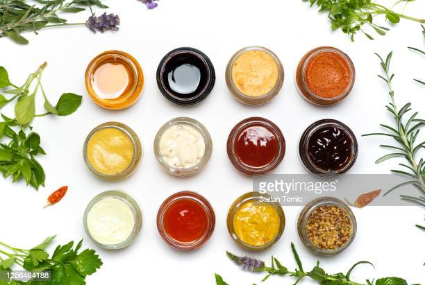 large collection of sauces and spiced spreads in small jars isolated flat lay - sauce stock pictures, royalty-free photos & images