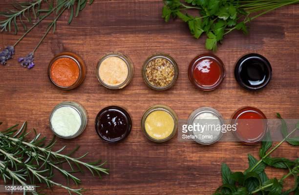 grande collection de sauces et de tartinades épicées dans de petits pots sur une table en bois - sauce photos et images de collection