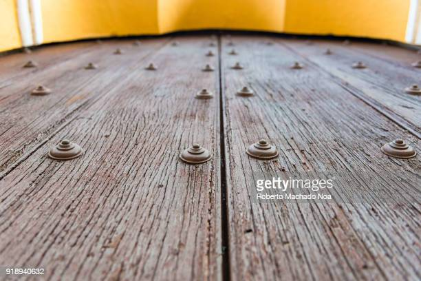 Large colonial wood door with rivets at the entrance of the Saint John the Baptist Catholic Church