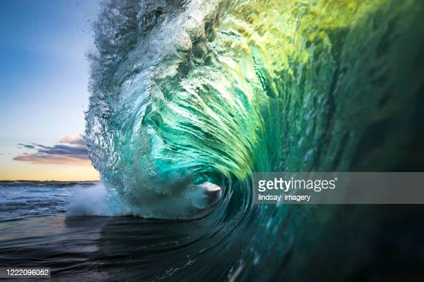 large colourful wave breaking in ocean over reef and rock - surf stock pictures, royalty-free photos & images
