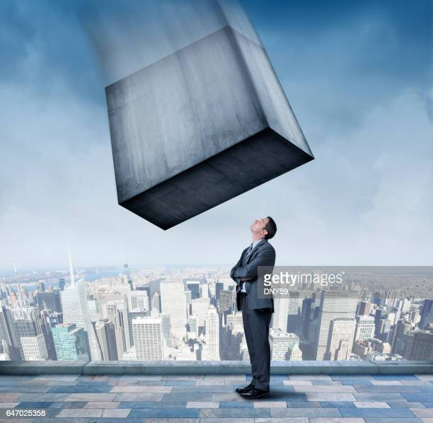 large concrete block about to fall on businessman - calm before the storm stock pictures, royalty-free photos & images