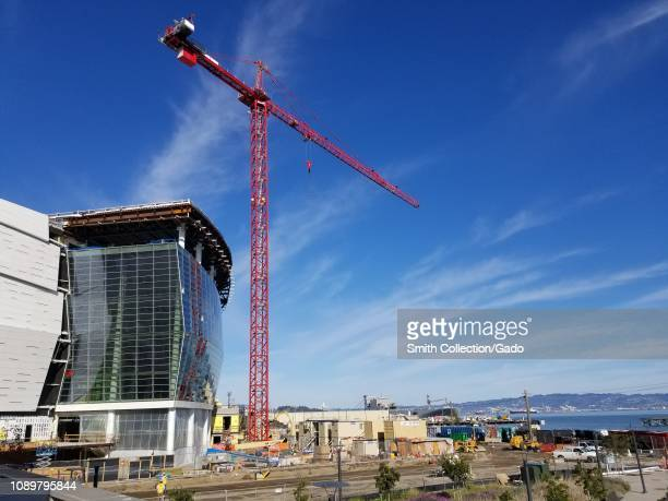 Large construction crane and partially completed glass main entrance are visible at Chase Center the new home of the Golden State Warriors basketball...