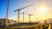 Large construction site including several cranes, with clear sky and the sun