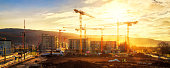 Large construction site including several cranes, with lots of gold sunlight