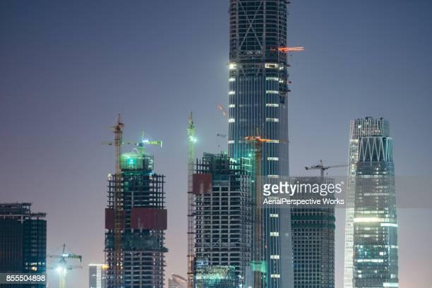 Grand chantier de construction de grues et de gratte-ciel dans la nuit