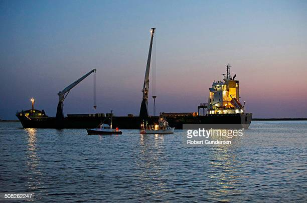 CONTENT] A large container ship near empty and accompanied by two smaller boats is shown offloading against a picturesque twilight sky in Cape Cod...
